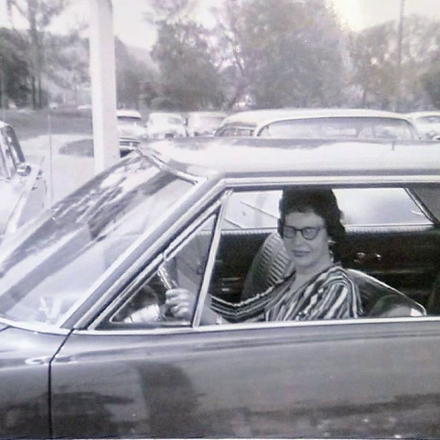 Woman wearing 60's style glasses sitting behind the steering wheel of a car