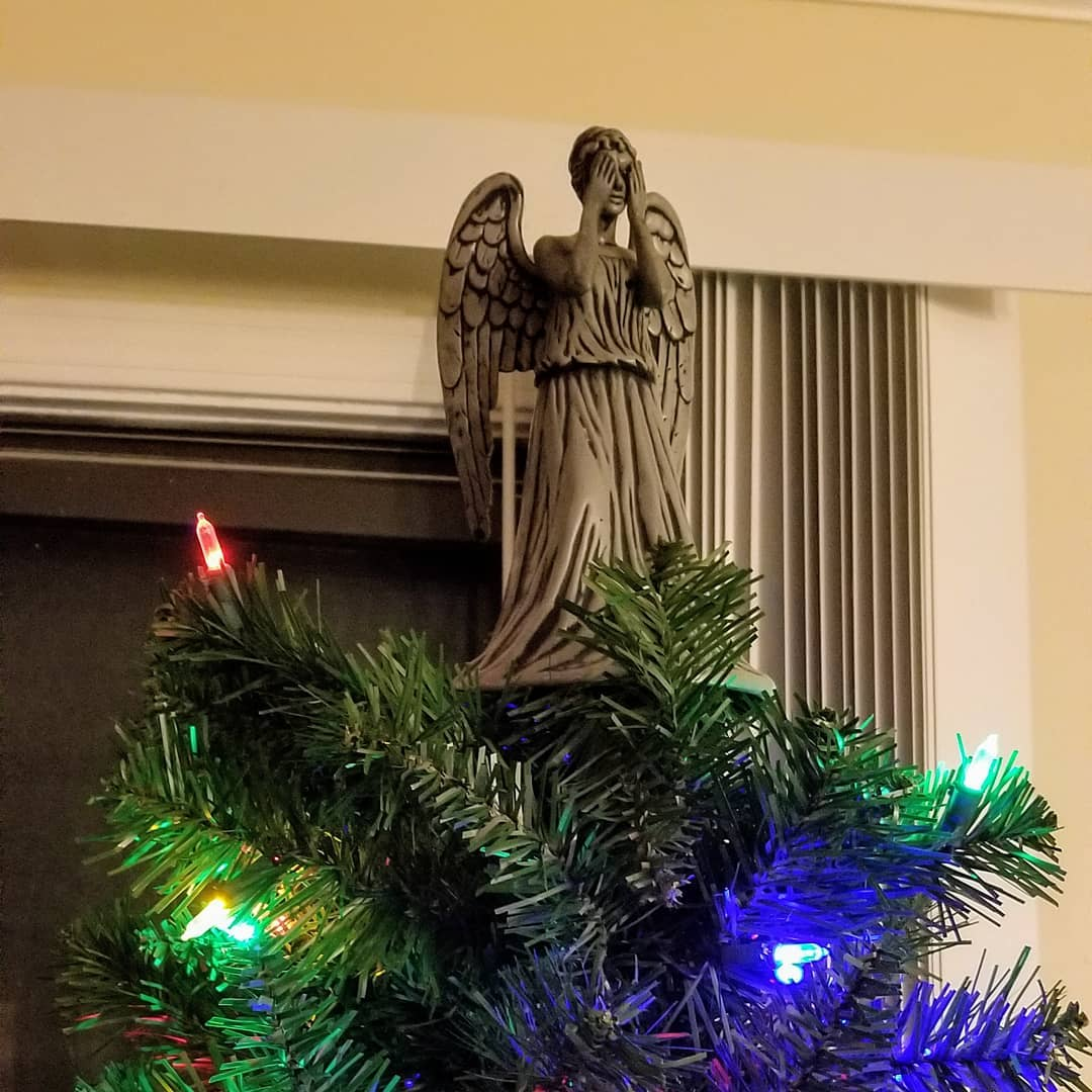 a weeping angel covering her eyes stands atop a Christmas tree with lights