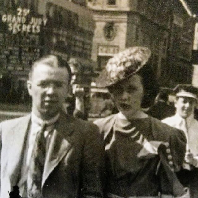 """Man and a woman on a street in New York City in front of a movie theater advertising 25 cent movie tickets to see """"Grand Jury Secrets"""""""
