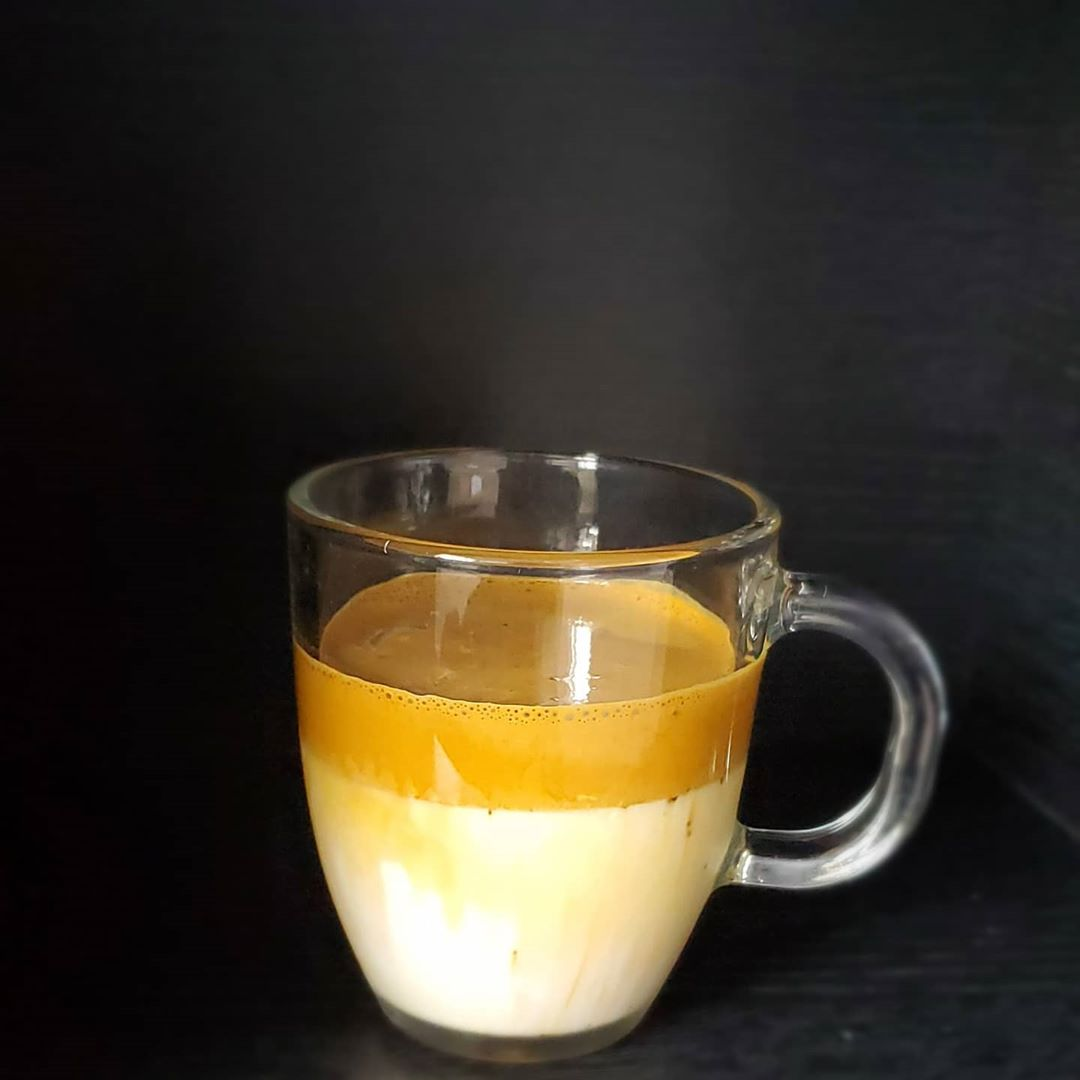 coffee cup filled with milk and a coffee foam on top