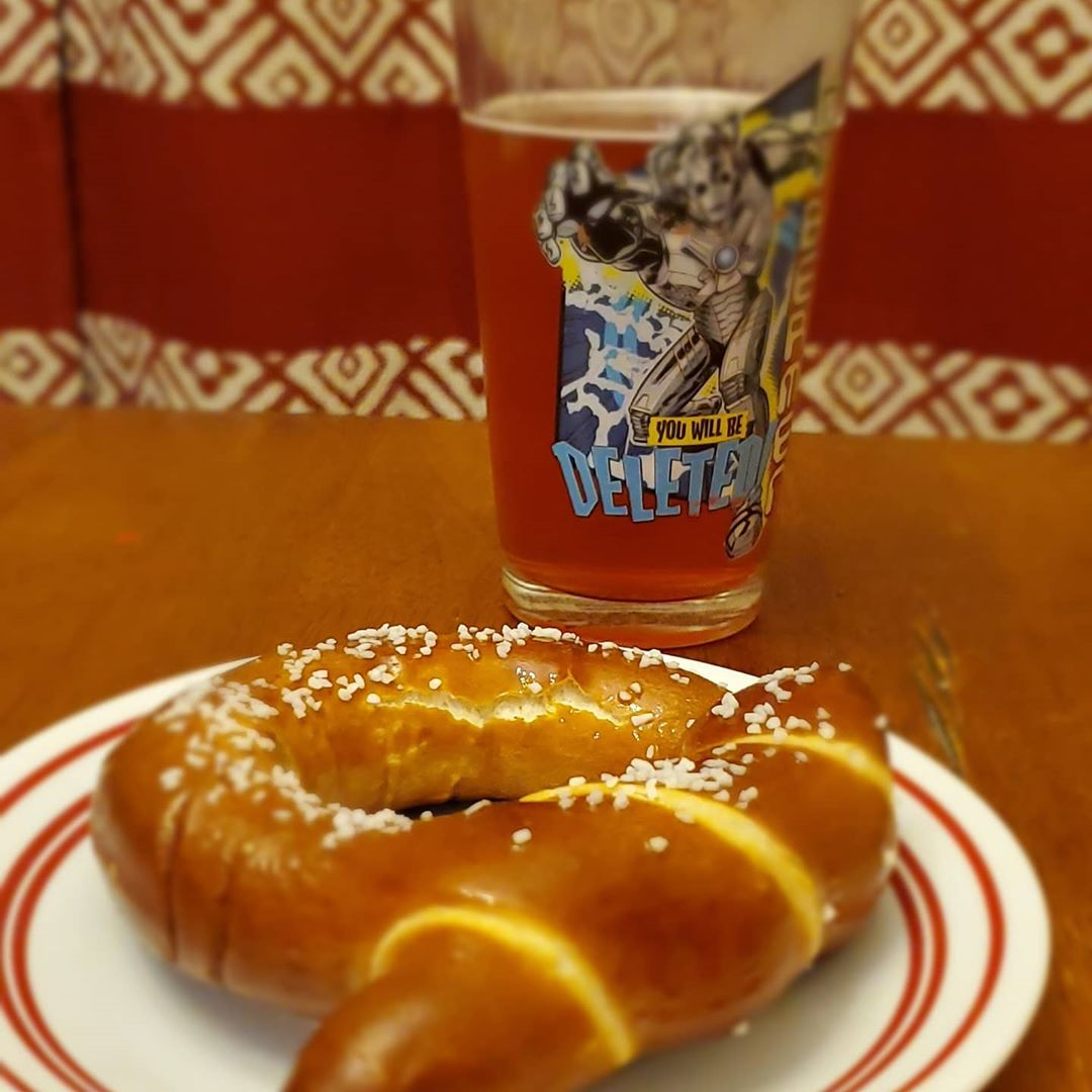 a glass of beer with a soft pretzel