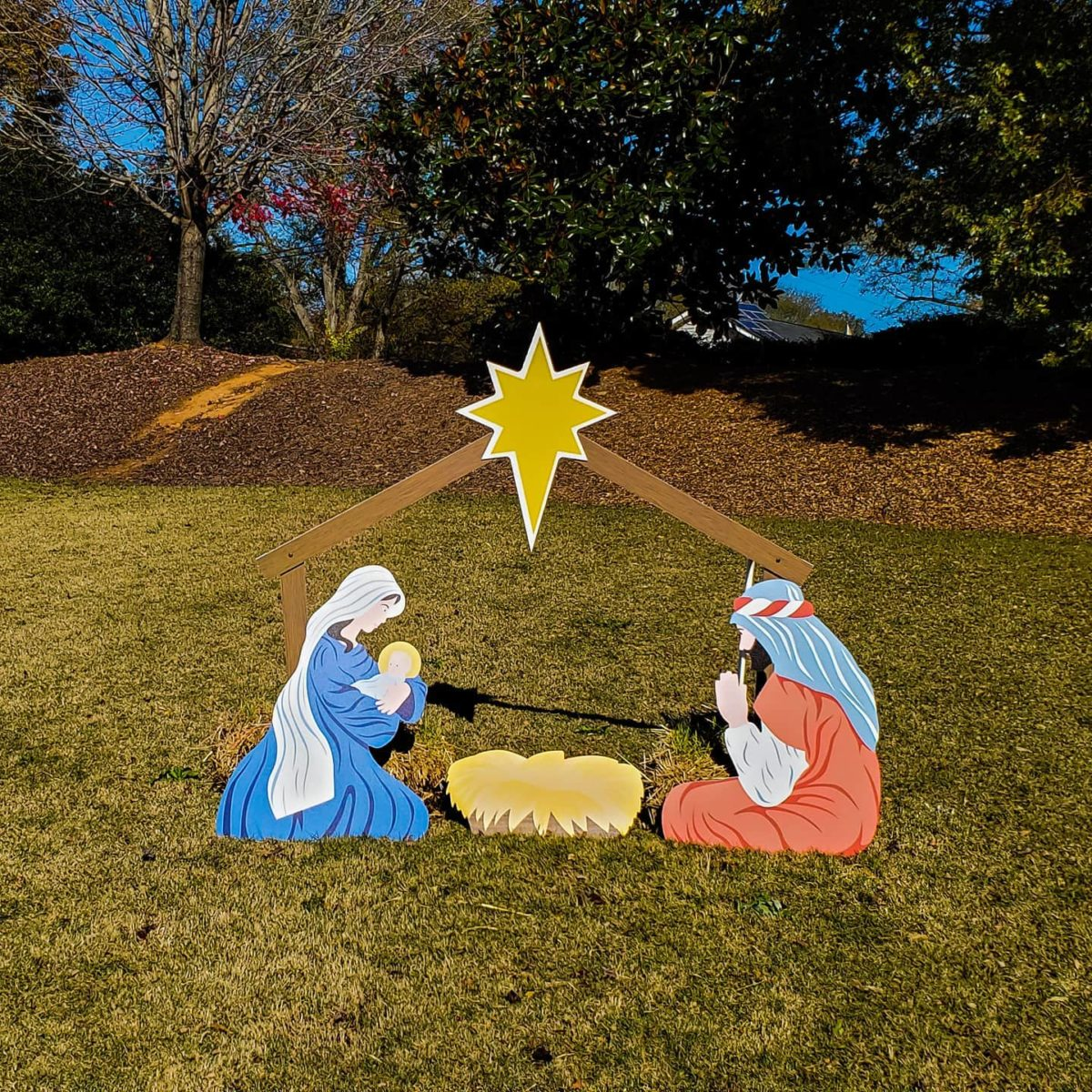 Manger scene with Mary, Joseph and baby Jesus. Barn and star above.